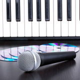 Microphone, cd and piano keyboard on black table Stock Images