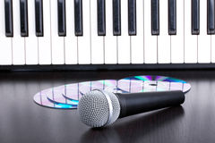 Microphone, cd and piano keyboard on black table Stock Photos