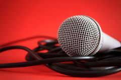 Microphone close up. Close up of professional metal silver microphone on red background Stock Photos