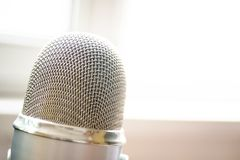 Microphone close up shot. In seminar, studio or meeting room in blur focus for copy space stock photography