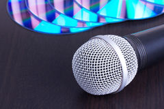 Microphone and compact disks on black table Stock Image