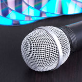 Microphone and compact disks on black table Royalty Free Stock Images