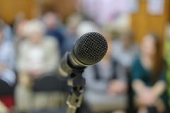 Microphone in concert hall or conference room with defocused bokeh lights in background. Extremely shallow dof. People in blur stock photos