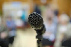 Microphone in concert hall or conference room with defocused bokeh lights in background. Extremely shallow dof. People in blur stock photography