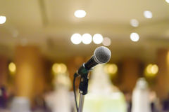 Microphone in concert hall or conference room with lights in bac Royalty Free Stock Photo