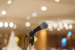 Microphone in concert hall or conference room with lights in bac Stock Photo