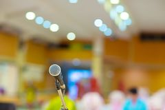 Microphone in concert hall or conference room soft and blur style for background. Microphone over the Abstract blurred photo of conference hall or seminar room Royalty Free Stock Images