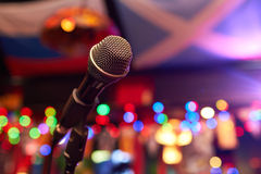 Microphone in concert hall. Or conference room with warm lights on background Stock Photo