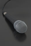 Microphone with cord. Close-up of vocal mike with cord on the black semiglossy surface stock image