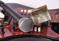 A microphone and dollar lying on a guitar Royalty Free Stock Photos