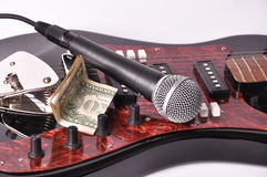 A microphone and dollar lying on a guitar Royalty Free Stock Photo