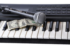 A microphone and dollar lying on the keys Stock Image