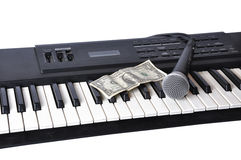 A microphone and dollar lying on the keys Royalty Free Stock Images