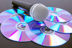 Microphone and dvd disks on black table Royalty Free Stock Image