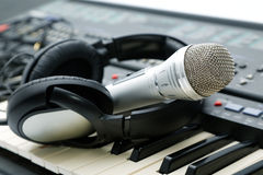 Microphone and ear-phones on the keyboard Stock Images