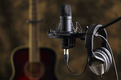 Microphone, earphones and acoustic guitar Stock Photo