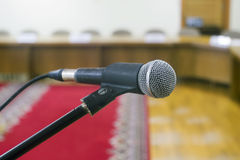 Microphone in an empty auditorium on background a red carpet. Royalty Free Stock Images