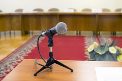Microphone in an empty auditorium on background a red carpet. Stock Photos