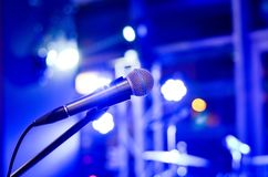Microphone on  empty  stage  with multi colored   blurred  background  lights. Close-up  of microphone on  empty  stage  with multi colored   blurred  background stock images