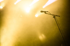 Microphone on empty stage waiting for a voice. With copyspace and back light royalty free stock photo