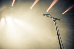 Microphone on empty stage waiting for a voice. With copyspace and back light Royalty Free Stock Photography