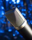 Microphone engrené par métal avec le bleu derrière Photographie stock