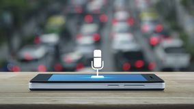Microphone flat icon on modern smart mobile phone screen on wooden table over blur of rush hour with cars and road in city, Busine. Microphone flat icon on stock video footage