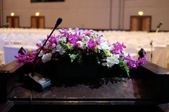 Microphone and flower bouquet on wooden podium. Close up microphone and flower bouquet on wooden podium in meeting room stock photos