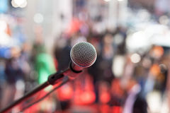 Microphone in focus against blurred audience Stock Photography