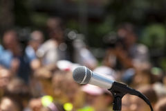 Microphone in focus against blurred audience Stock Image