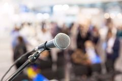 Microphone in focus against blurred audience. News conference. Royalty Free Stock Photography