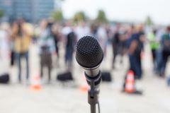 Microphone in focus against blurred people. News conference. Royalty Free Stock Image