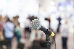 Microphone in focus against blurred audience. Press conference. Stock Photo
