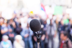Microphone in focus, against blurred crowd Royalty Free Stock Photography