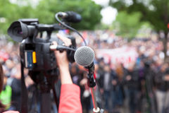 Microphone in focus against blurred crowd. Filming protest. Filming public demonstration with a video camera. Street protest Royalty Free Stock Photo