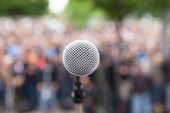 Microphone in focus against blurred crowd. Political rally. Political protest. Public demonstration. Microphone stock photography