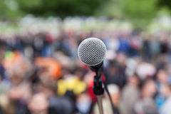 Microphone in focus against blurred crowd. Protest. Stock Photos
