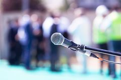 Microphone in focus against blurred group of people Royalty Free Stock Images