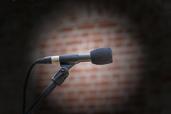 Microphone in front of an old blurred brick wall with a light sp Stock Photography