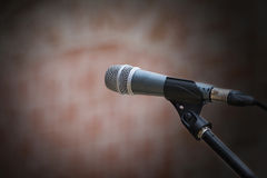 Microphone in front of an old blurred brick wall with a light sp Stock Images