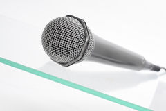 Microphone on the glass table. Microphone isolated on the glass table Royalty Free Stock Photos