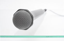 Microphone on the glass table. Microphone isolated on the glass table Stock Image