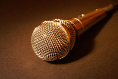 Microphone in gold. Microphone on dark background in blue spot lights Royalty Free Stock Image