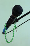Microphone on a green background and rosary. Microphone on a green background Royalty Free Stock Photography