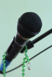 Microphone on a green background and rosary. Microphone on a green background Royalty Free Stock Photos