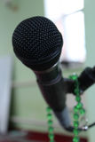 Microphone on a green background and rosary. Microphone on a green background and light Stock Photo