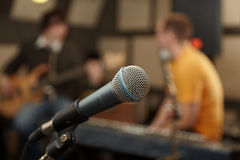 Microphone. guitar player and keyboarder in out of focus Royalty Free Stock Image