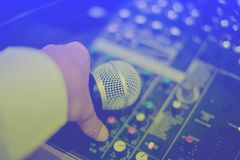 Microphone in hand and adjust an audio mixer controller in the c royalty free stock photography