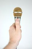 Microphone in hand offering mic. Mic in hand Royalty Free Stock Images