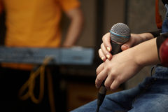 Microphone in hand of vocalist girl. Stock Photo